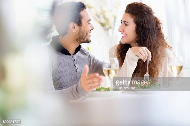 Smiling couple eating at table