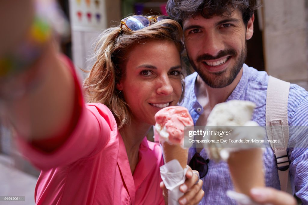 Smiling couple eating ice cream cones taking selfie on street in Barcelona : Stock Photo