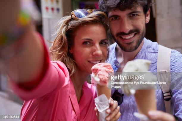 Smiling couple eating ice cream cones taking selfie on street in Barcelona