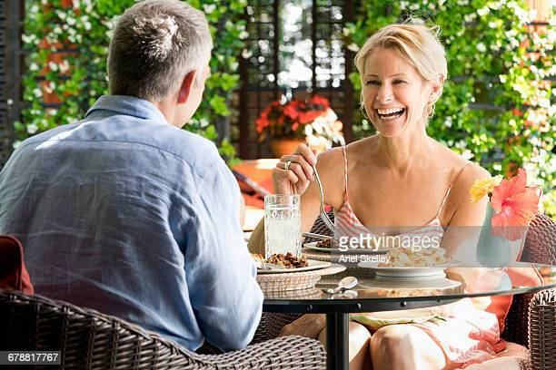 Smiling couple eating in garden