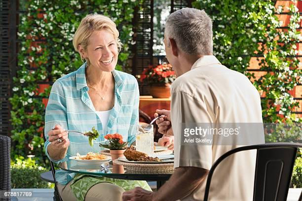 Smiling couple eating in garden