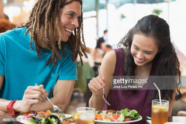 Smiling couple eating lunch in cafe