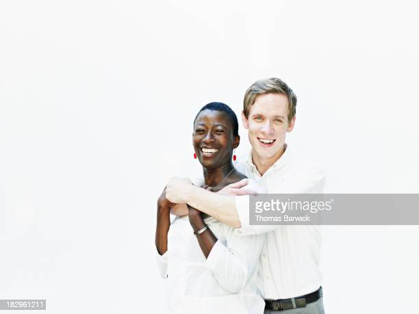 Smiling couple embracing against white background