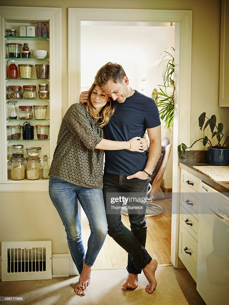Smiling couple embracing in doorway of kitchen : Stock Photo