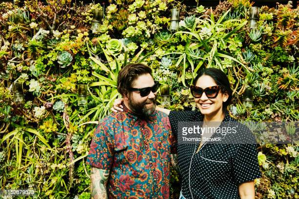 smiling couple embracing in front of living wall - bonding stock pictures, royalty-free photos & images