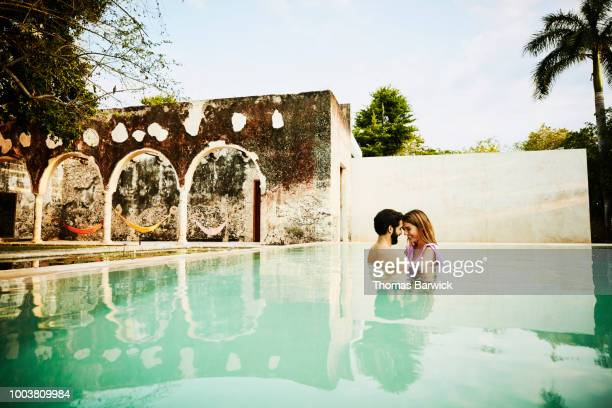Smiling couple embracing in pool during romantic vacation at luxury tropical resort