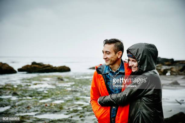 Smiling couple embracing on beach