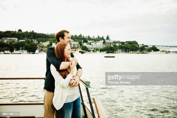 Smiling couple embracing on boat during cruise on summer evening