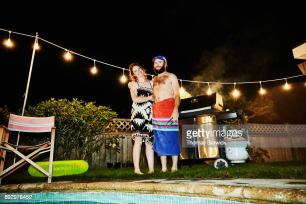 Smiling couple embracing while grilling on barbecue for friends during party on summer evening