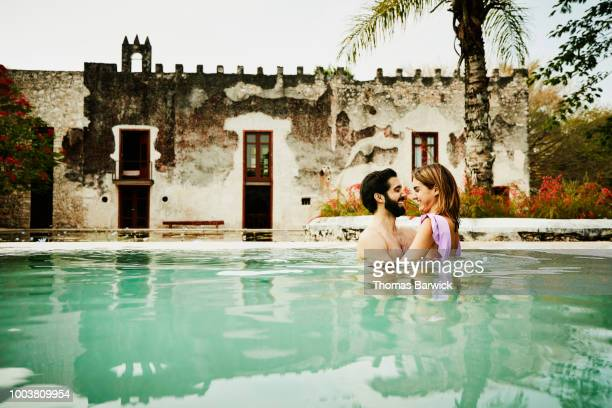 Smiling couple embracing while relaxing in pool at luxury tropical resort
