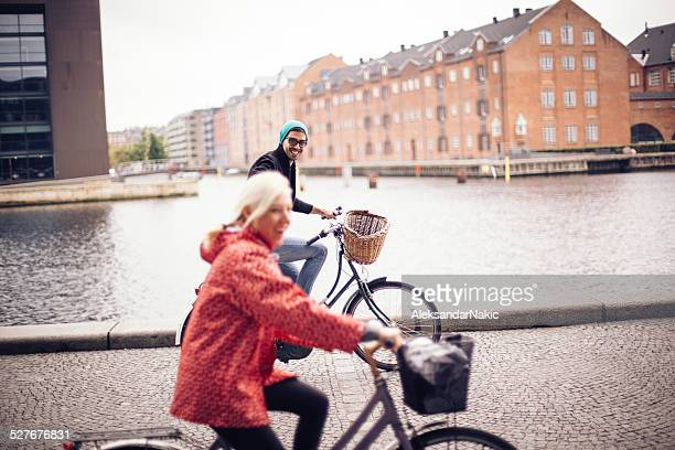 Smiling couple enjoying the bicycle ride on a gloomy day