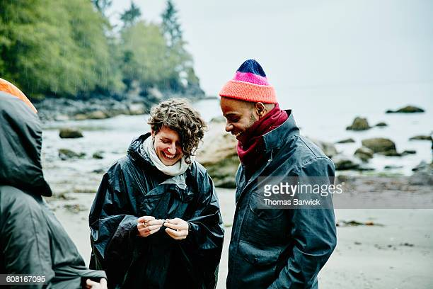 Smiling couple exploring beach in the rain