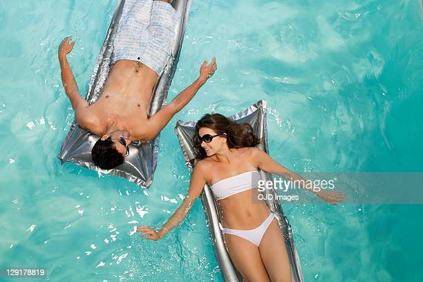 smiling couple floating in pool - swimwear stock pictures, royalty-free photos & images