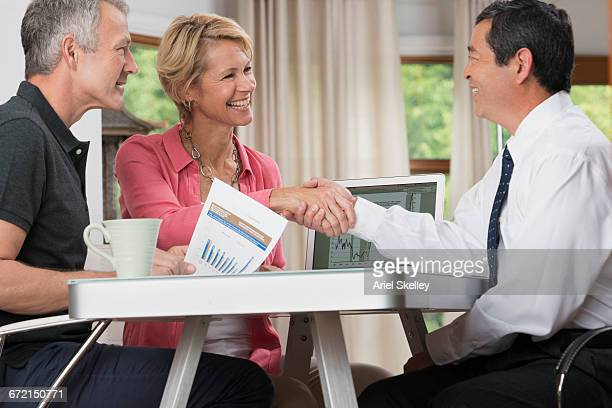 Smiling couple handshaking with financial advisor at table