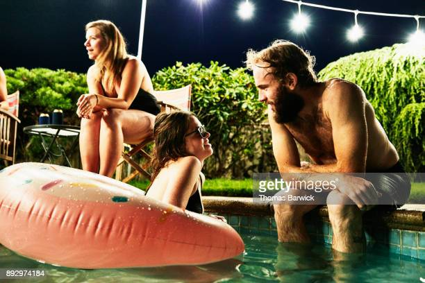 Smiling couple hanging out in pool during backyard party with friends on summer evening