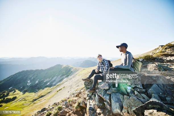 smiling couple hanging out on rocks during early morning hike in mountains - holiday stock pictures, royalty-free photos & images