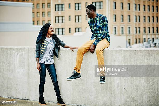 Smiling couple hanging out on rooftop of building