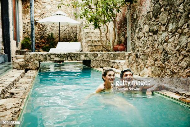Smiling couple hanging out together in pool in courtyard of boutique hotel
