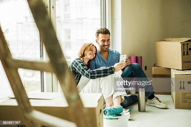 Smiling couple having a break from renovating