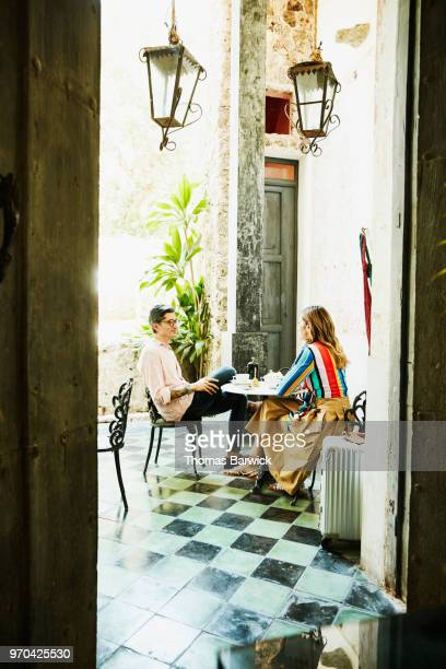 Smiling couple having coffee out outdoor cafe during vacation