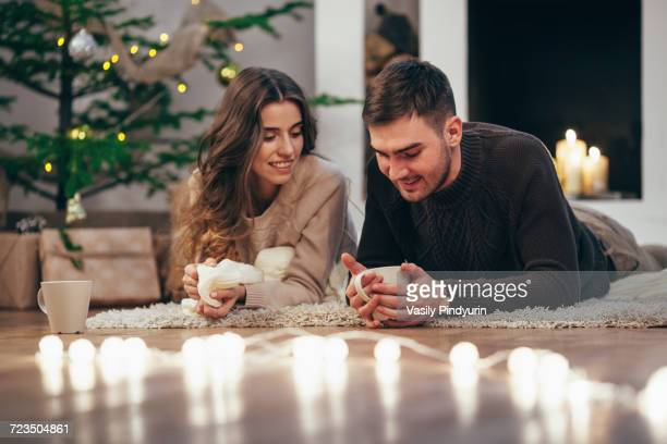 Smiling couple having coffee while lying on rug at home during Christmas