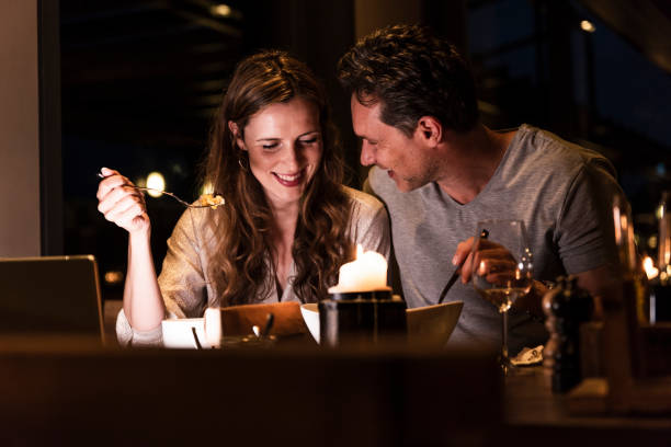 smiling couple having dinner together - couples romance stock pictures, royalty-free photos & images