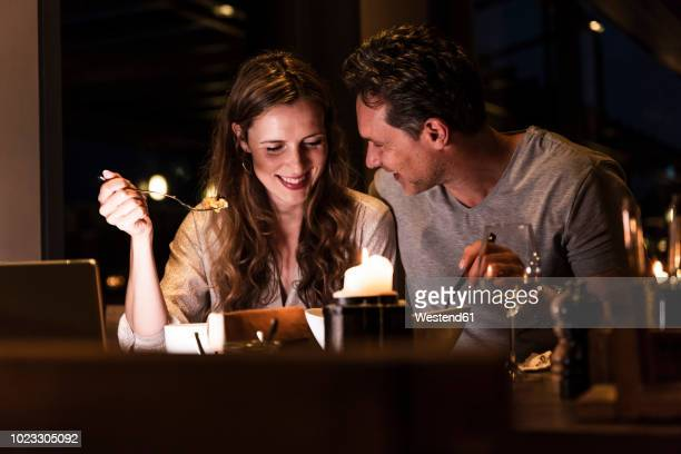 smiling couple having dinner together - warmes abendessen stock-fotos und bilder