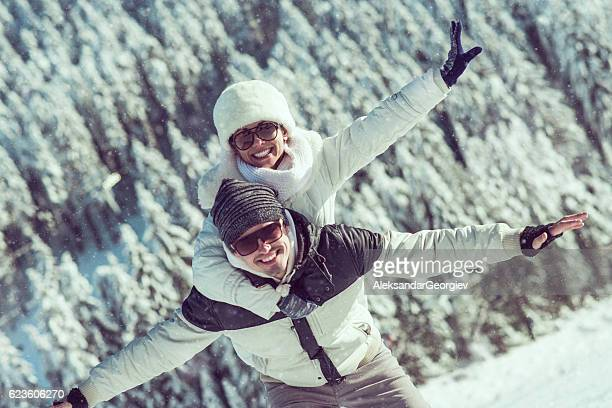 Smiling Couple Having Fun with Piggyback Ride on the Snow