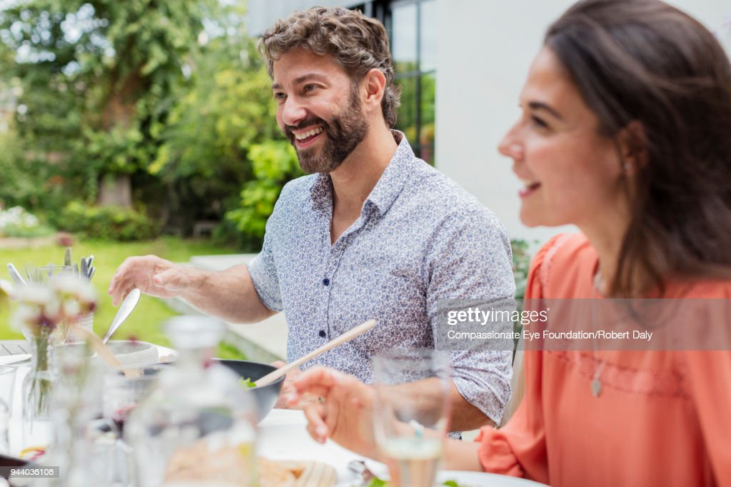Smiling couple having lunch on garden patio : Stock Photo