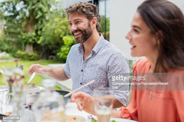 Smiling couple having lunch on garden patio
