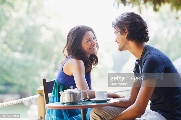 smiling couple having tea outdoors - couples dating stock pictures, royalty-free photos & images