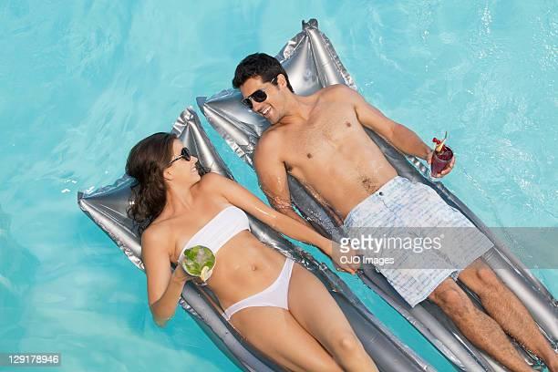 Souriant couple tenant le verre en vous détendant sur un radeau