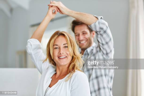 smiling couple holding hands and dancing together at home - mid adult couple stock pictures, royalty-free photos & images