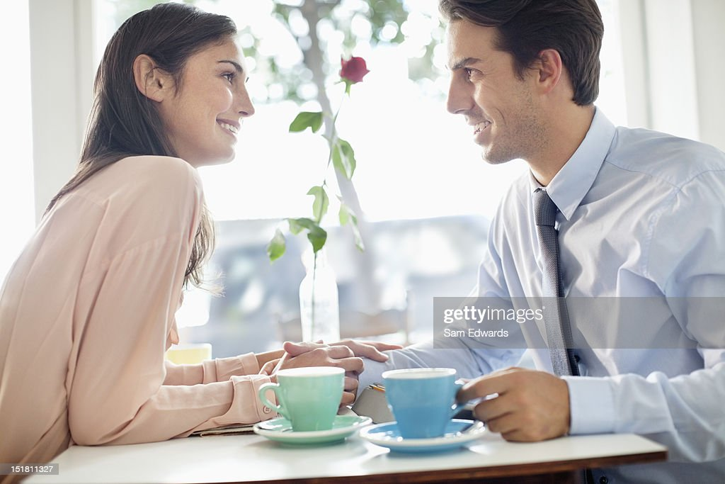 Smiling couple holding hands and drinking coffee in cafe : Stock Photo