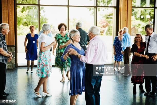 Smiling couple holding hands and finishing dance in community center