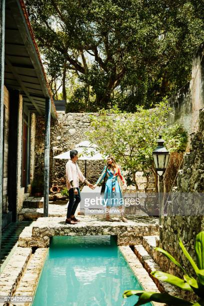 Smiling couple holding hands and walking across bridge over pool in courtyard of boutique hotel