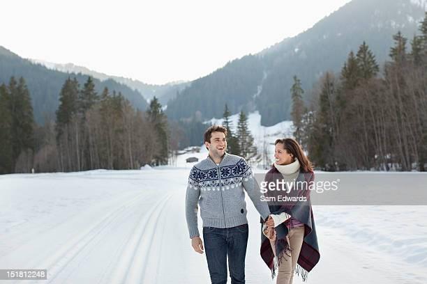 Sonriente pareja sosteniendo las manos y caminar en campo nival