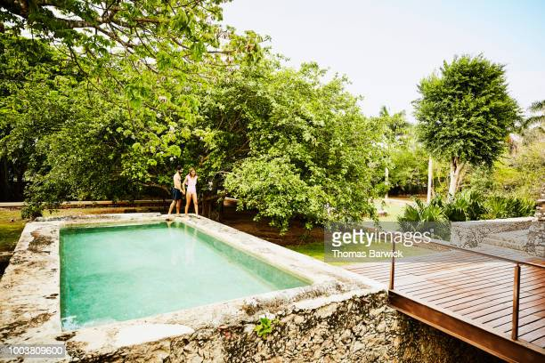 Smiling couple holding hands and walking on edge of plunge pool outside of bungalow at luxury tropical resort