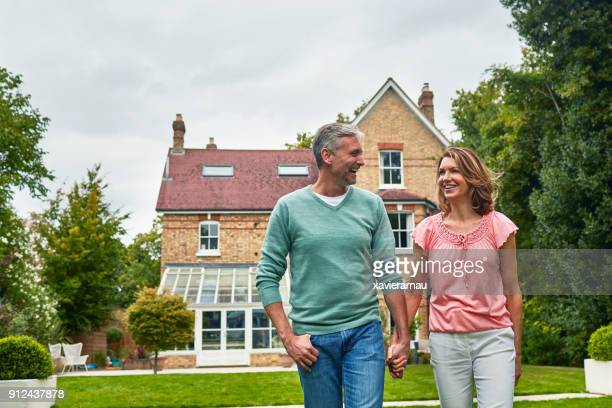 Smiling couple holding hands in front of house
