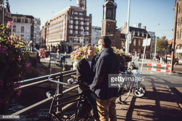 Souriant couple main dans la main sur le pont, la jeune fille est assise sur le vélo