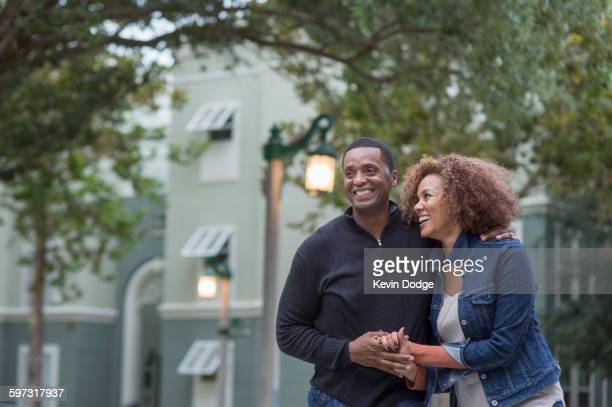 smiling couple holding hands outdoors - mid adult stock pictures, royalty-free photos & images