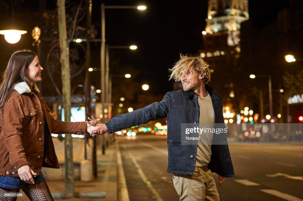 Smiling couple holding hands while crossing street : Stock Photo