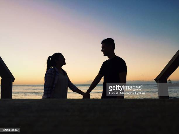 Smiling Couple Holding Hands While Standing At Beach Against Sky During Sunset