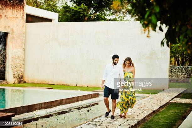 Smiling couple holding hands while walking to dinner on grounds of luxury resort
