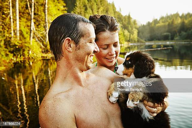 Smiling couple holding puppy on dock in lake
