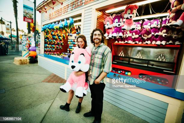 smiling couple holding stuffed animal after winning carnival game at amusement park - traveling carnival stock pictures, royalty-free photos & images