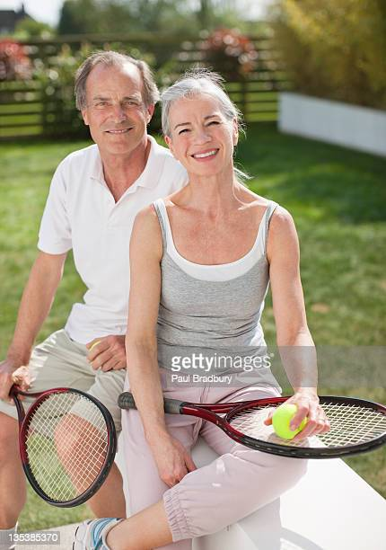 Smiling couple holding tennis rackets
