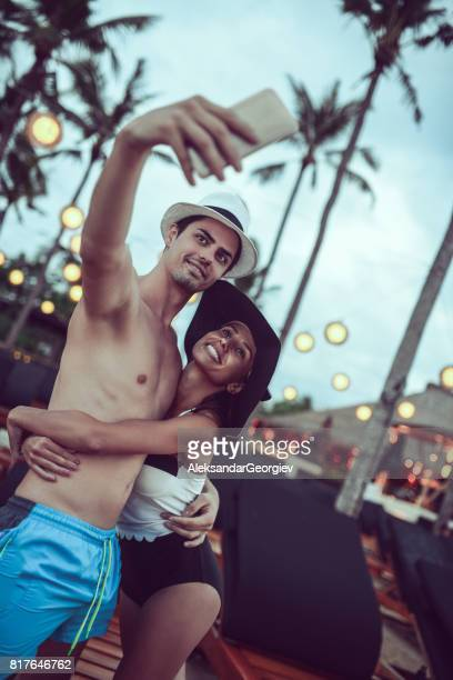 Smiling Couple how Taking Selfie on Summer Beach Party