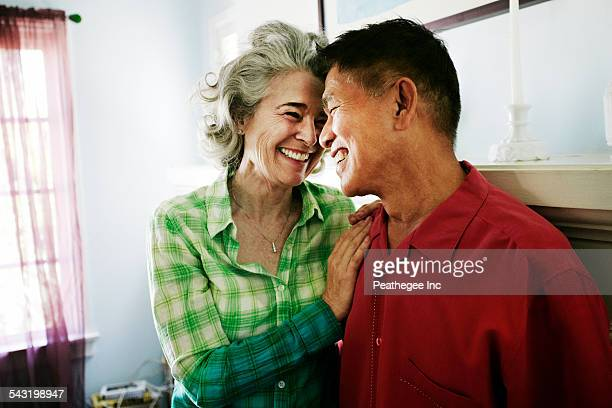 Smiling couple hugging in living room