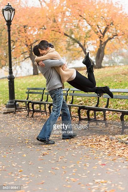 smiling couple hugging in park - homem pegando mulher imagens e fotografias de stock